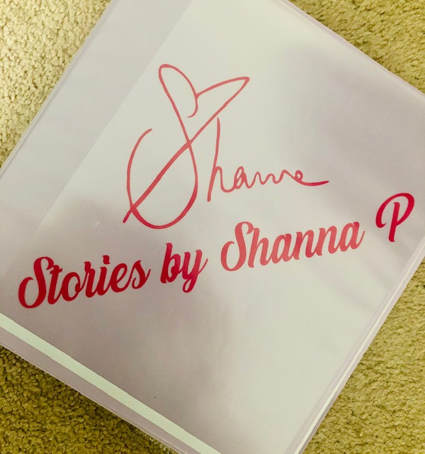 """A pink binder with the words """"Stories by Shanna P"""" in red, with Shanna Pikora's signature."""