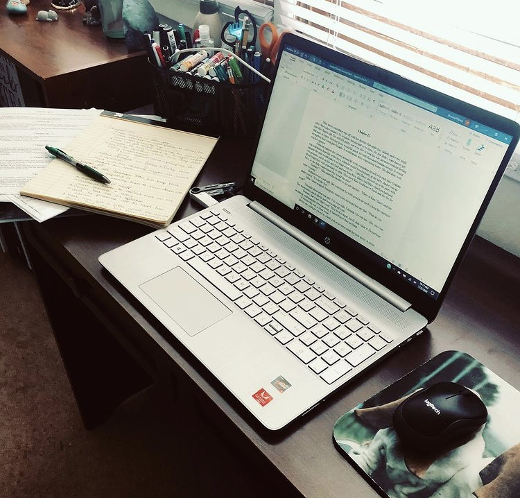 A picture of an office desk, dark brown. There is a computer open, showing a page of a manuscript draft. To the left of the computer is a binder and piles of papers and steno pads with notes.