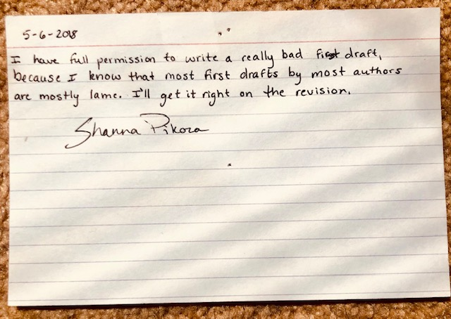 A lined notecard with the following written on it: 5/6/2018. I have full permission to write a really bad first draft, because I know that most first drafts by most authors are mostly lame. I'll get it right on the revision. Shanna Pikora.
